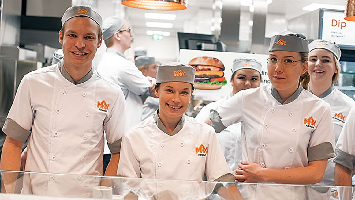 MAX Staff in the kitchen behind a counter. Three woman and one man smiling. Photo