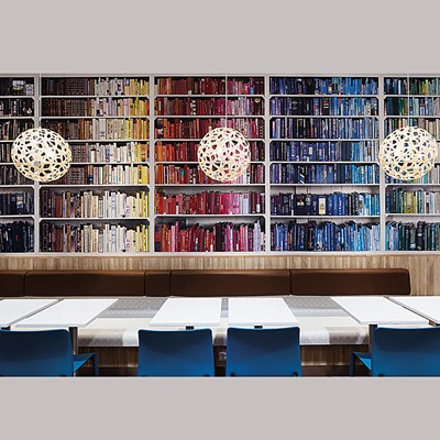 Interior showing a wall of colourful books, lamps and tables. Interior at a MAX restaurant. Photo