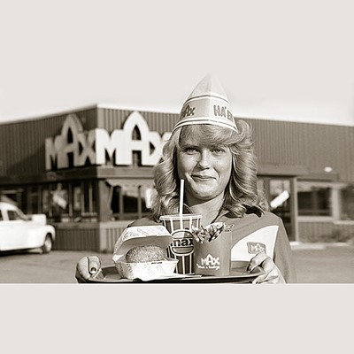 Waitress with tray with MAX-burger meal in front of MAX restaurant. Old foto in black and white